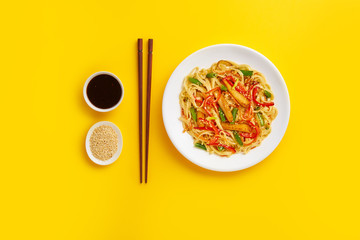 Noodles with fried chicken and vegetables on a yellow background. Flat lay with top view and copy space