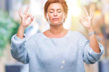 Atrractive senior caucasian redhead woman wearing winter sweater over isolated background relax and smiling with eyes closed doing meditation gesture with fingers. Yoga concept.
