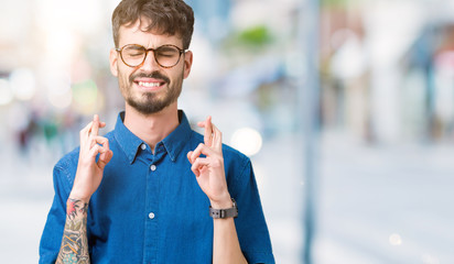 Young handsome man wearing glasses over isolated background smiling crossing fingers with hope and eyes closed. Luck and superstitious concept.