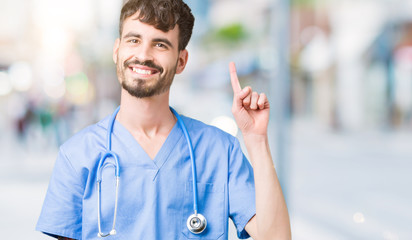 Young handsome nurse man wearing surgeon uniform over isolated background showing and pointing up with finger number one while smiling confident and happy.
