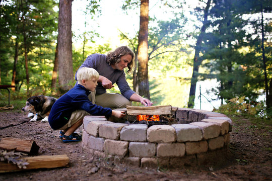 Father and Son Starting Campfire in Fire Ring at Campground Overlooking a Lake in the Woods