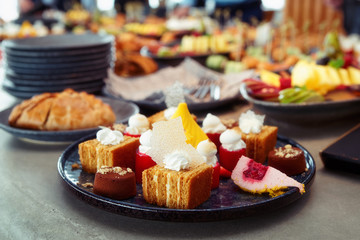 Desserts, fruits and other food on banquet table, toned