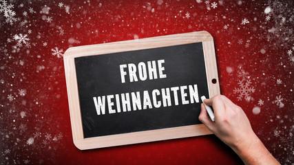 """Hand schreibt """"Frohe Weihnachten"""" auf Kreidetafel vor rotem Hintergrund"""