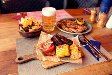 Grilled meat, corn, potato chips and beer, toned