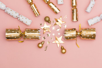 christmas crackers luxury gold festive cracker on a pastel pink background