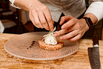 Cook is decorating salmon tartar with apple, toned