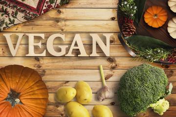 """Zutaten zum kochen und das Wort """"vegan"""" in Holzbuchstaben auf Holzhintergrund"""
