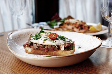 Sandwich with beef tartar and fried egg, toned image