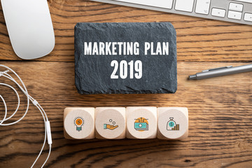 """slate plate with message """"marketing plan 2019"""" on wooden background surrounded by office stuff"""