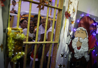"""Prisoners look through the bars of their prison cell during a Christmas decorating event """"Bright prison cell"""" at the Nelson Hungria prison in Rio de Janeiro"""