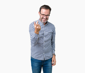Handsome middle age elegant senior man wearing glasses over isolated background Beckoning come here gesture with hand inviting happy and smiling