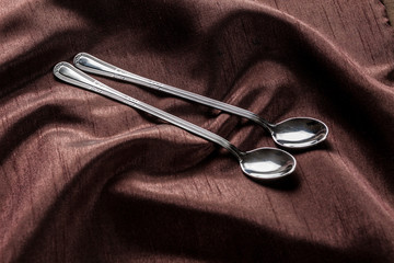 Long spoons on chocolate brown fabric