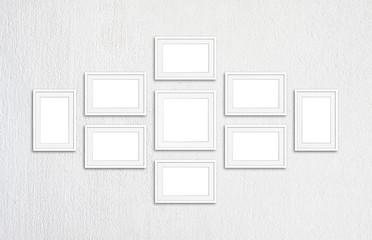 Frames collage. Nine blank frameworks on white plastered textured wall.