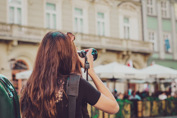 a girl with long hair holds a camera with a large owl and takes pictures in the tourist center of the old city. back view