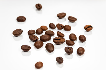 Coffe beans isolated on reflective white surface