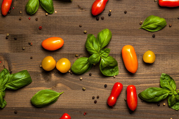 Basil, pepper and cherry tomatoes composition, on dark wooden table
