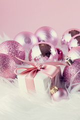 Pink Christmas decorations with gift box on white fur background, retro toned