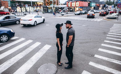 couple man and women in black hats standing crosswalk in the evening city street.