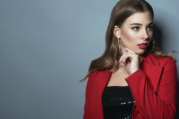 Portrait of beautiful lady with perfect make up and shiny hair tucked behind her ear wearing black sequin top and bright red jacket looking aside. Isolated on blue background. Text space.