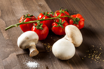 Cherry tomates and mushrooms on brown cutting board