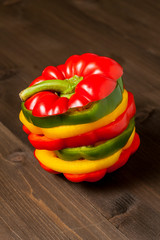 Fresh bell pepper slices isolated on wooden cutting board