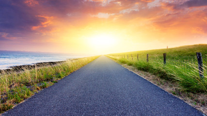 Paved country road . Landscape over clouds sunrise . Sunset above road .  Fototapete