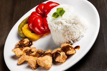 Chinese food on a white plate with rice, paprika and chicken