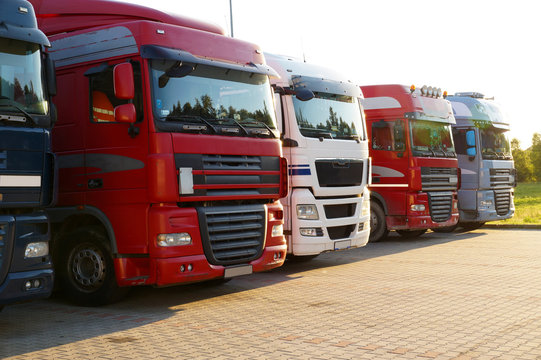 Transportation. Several trucks lined up in a row on a parking lot.