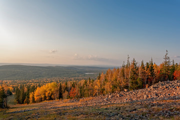 Autumn landscape view from the top of the mountain to the colorful autumn forest at sunset.