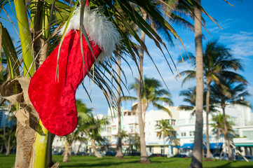 Christmas stocking hanging from palm tree in front of bright tropical holiday scene in South Beach, Miami, Florida, USA