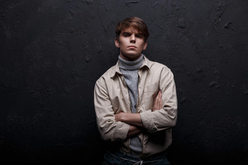 Young stylish man with a fashionable hairstyle in a jacket in gray sweater golf in cool blue jeans posing and looking at the camera in a studio near the wall. American cute guy. Men's modern fashion.
