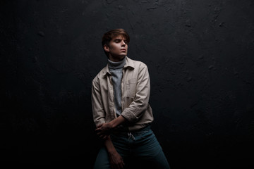 Stylish nice attractive young man with a fashionable hairstyle in a fashionable jacket in a gray sweater in stylish vintage blue jeans posing indoors near a black wall. American modern guy model