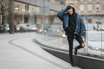Fashionable man walk on the street near buildings. Wear blue jacket and all black. Winter, autumn outfit. Jacket with blouse and black sneakers.