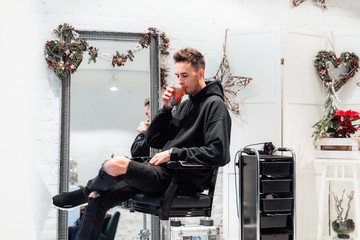 Fashionable man sit at hair salon with cup of tea. Wear blue jacket and all black. Winter, autumn outfit. Jacket with blouse and black sneakers.