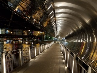 Chicago, Illinois 10-08-2016 Reflective curved metal walls and ceilings of the Chicago Riverwalk underpasses at night.