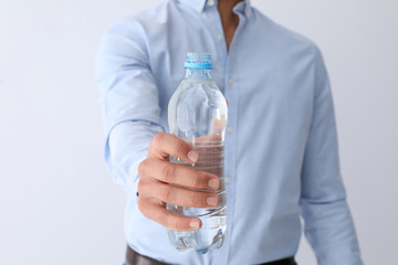 Man holding bottle of pure water on white background, closeup