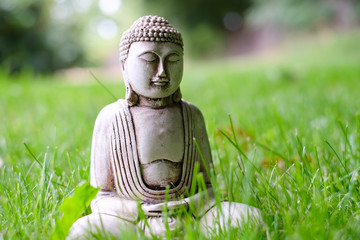 Small white Buddha statue in a meditation pose on green natural bright background. Religious symbol of buddhism