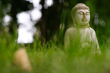Small white Buddha statue in a meditation pose with green grass foreground and on natural bright blurred background. Religious symbol of buddhism. Selective focus