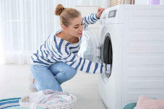 Young woman using washing machine at home. Laundry day