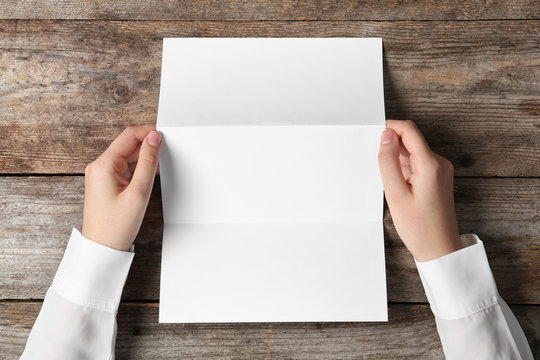 Woman holding blank brochure mock up on wooden table, top view