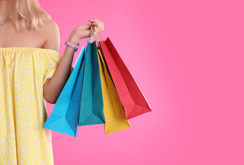 Young woman with shopping bags on color background, closeup. Space for text