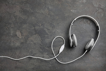 Stylish modern headphones and space for text on concrete background, top view