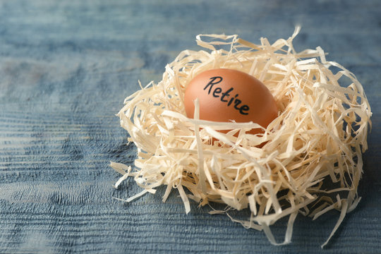 Egg with word RETIRE in nest on wooden background. Pension concept