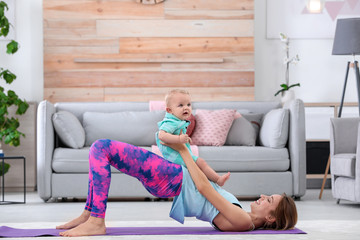 Young sportive woman doing exercise with her son at home. Fitness training