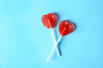 Heart shaped lollipops on color background, top view. Sweet love