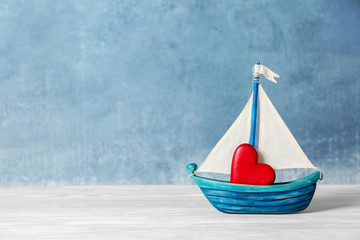 Toy ship with red decorative heart on table. Space for text Fototapete