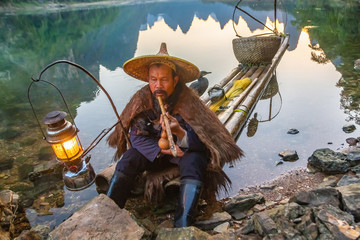 Chinese cormorant fisherman on raft in lake with a lighted lantern, a pipe, and fishing gear in Guilin, China.