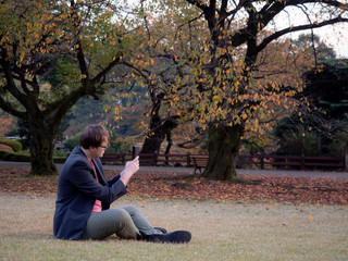 A man taking pictures of the Autumn scenery on his smartphone