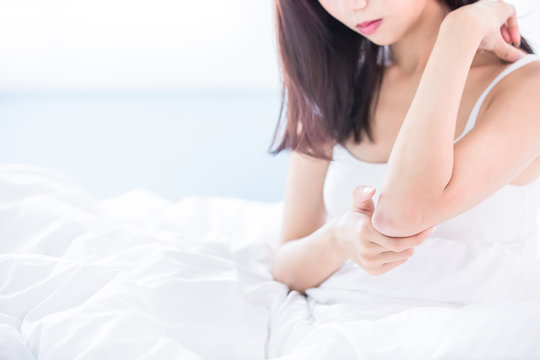 woman scratching arm and elbow