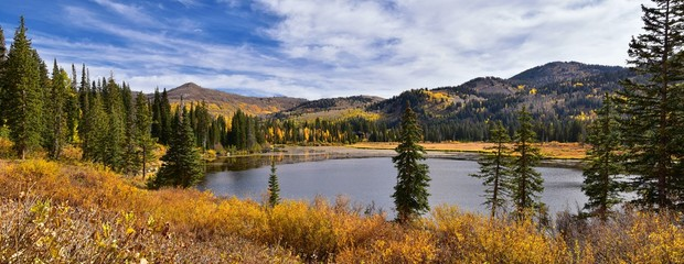 Silver Lake by Solitude and Brighton Ski resort in Big Cottonwood Canyon. Panoramic Views from the hiking and boardwalk trails of the surrounding mountains, aspen and pine trees in brilliant fall autu